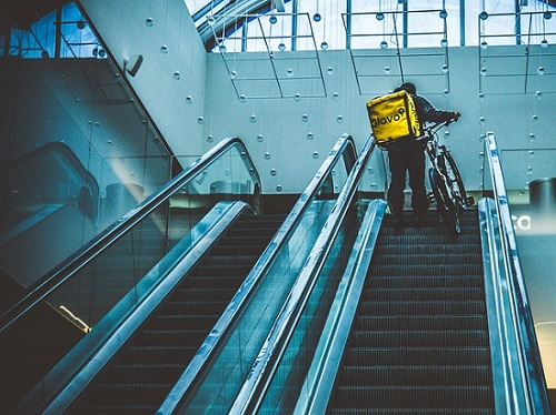 delivery rider on escalator